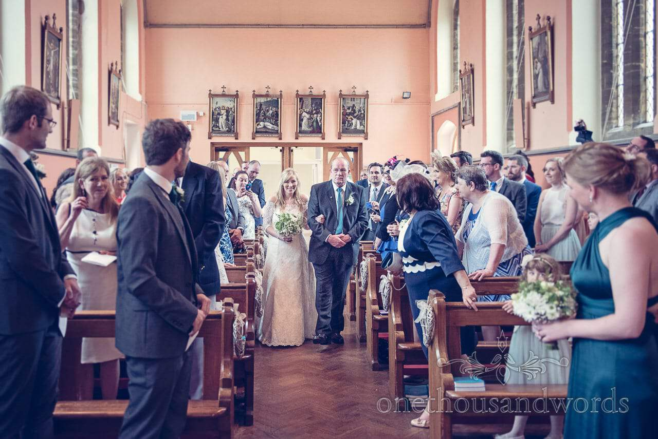 Bride and father of teh bride walk up the aisle at Sherborne Catholic church wedding