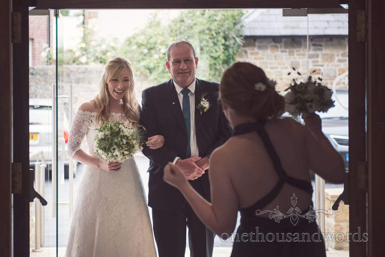 Bride and father of the bride laugh before entering catholic wedding ceremony