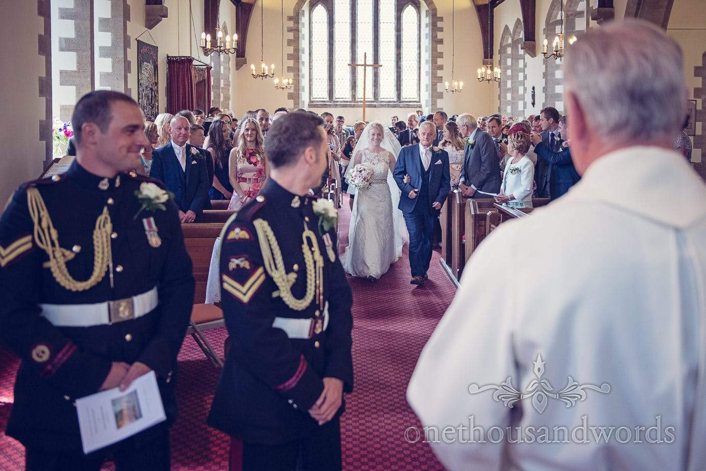 Bride and father of the bride walk up the aisle at Swanage Church wedding