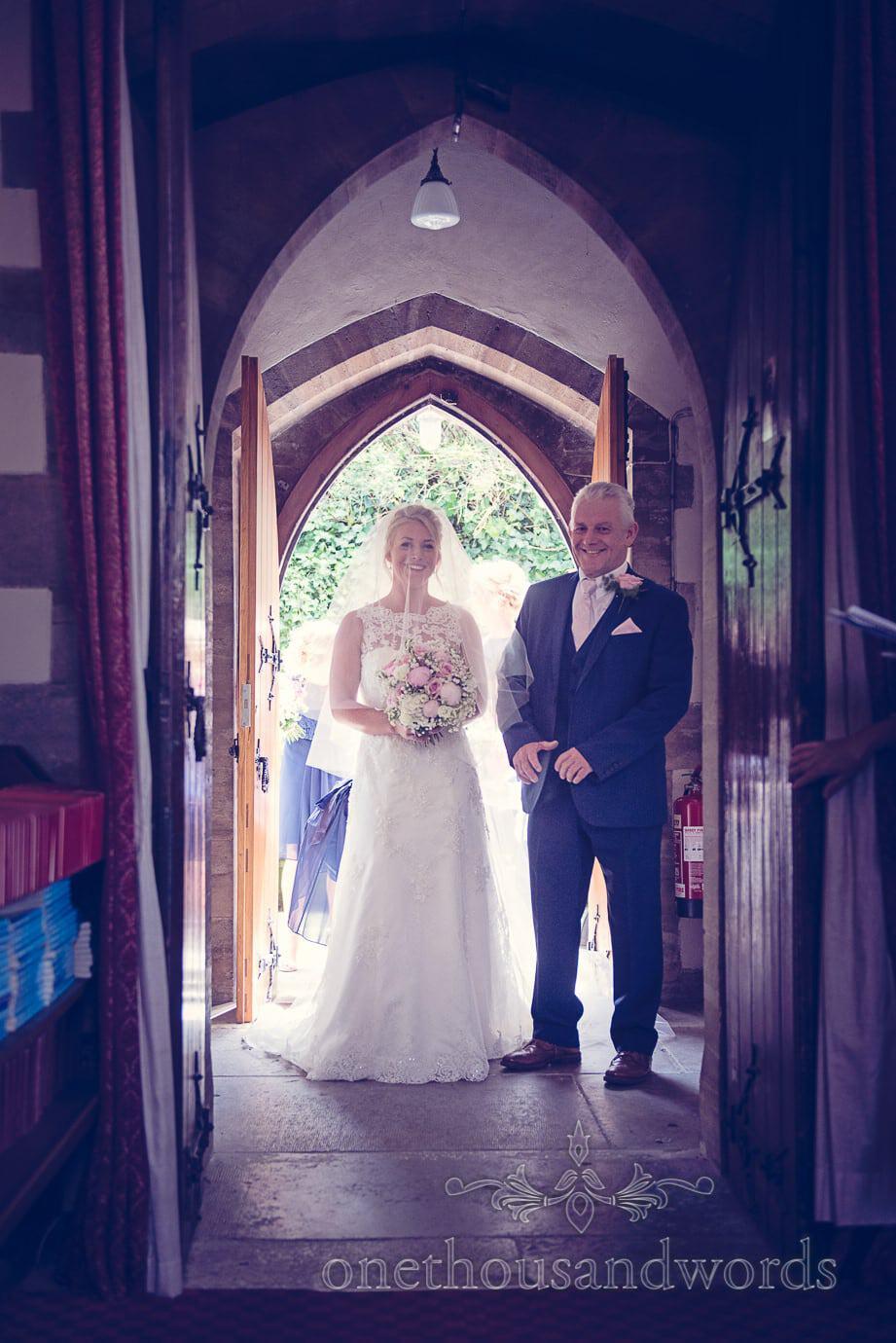 Bride and father wait under Swanage church arched doorways