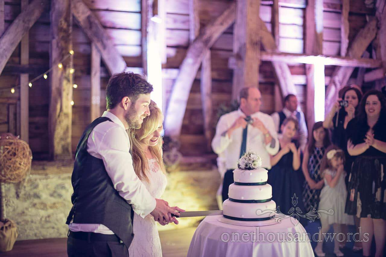Bride and groom cut the cake at barn wedding venue in Dorset