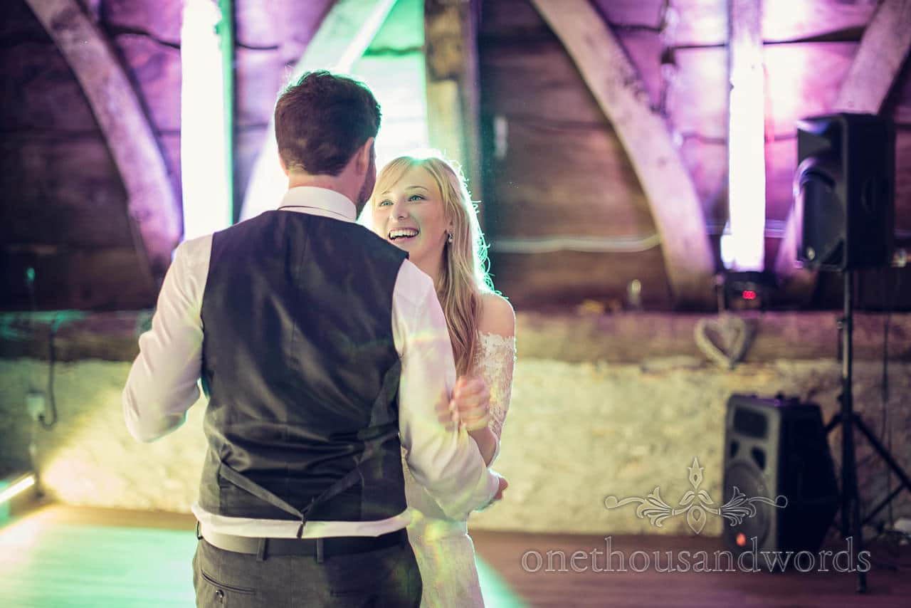 Bride and groom dance their first dance at Barn wedding venue with purple and green lighting