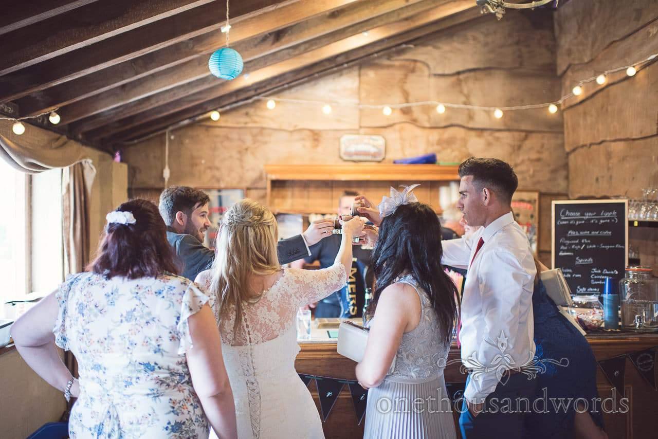 Bride and groom drink toast in Dorset barn wedding venue wooden bar