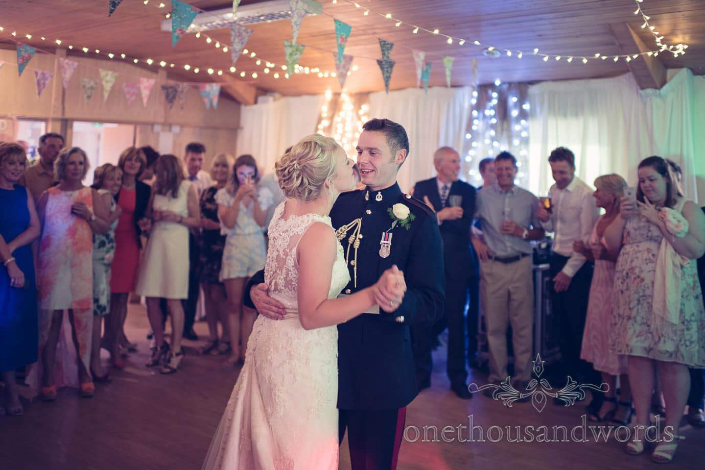 Bride and groom in military uniform dance first dance under bunting and fairy lights