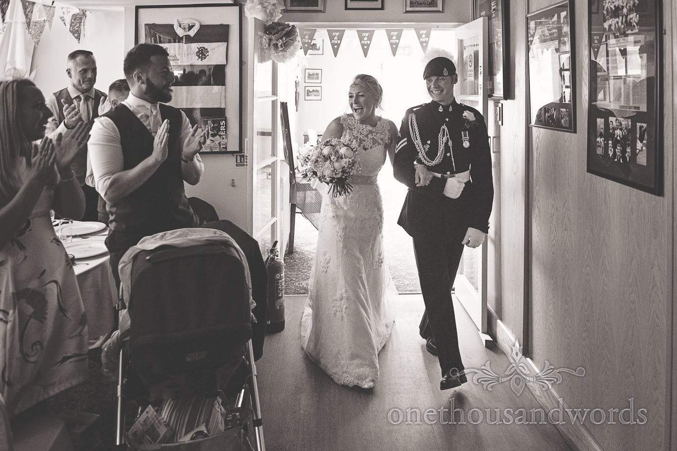 Bride and groom in military uniform enter wedding breakfast to applause