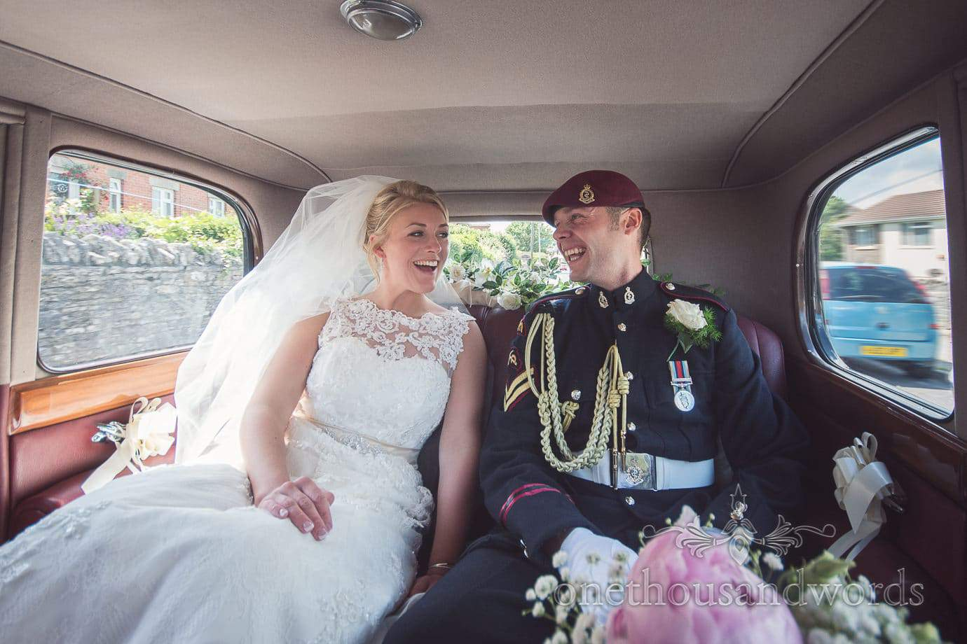 Bride and groom in Military uniform in Classic wedding car in Swanage