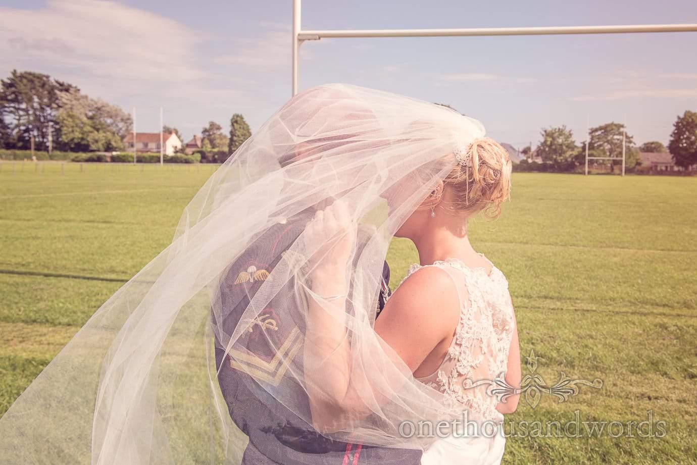 Bride and Groom Kiss under veil at Wareham Rugby Club Wedding