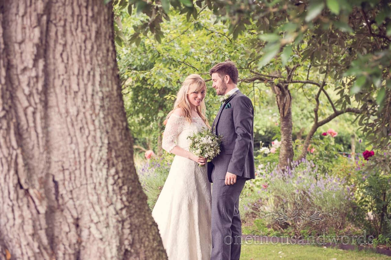 Bride and groom portrait in wooded flower garden at Stockbridge Farm Barn wedding venue