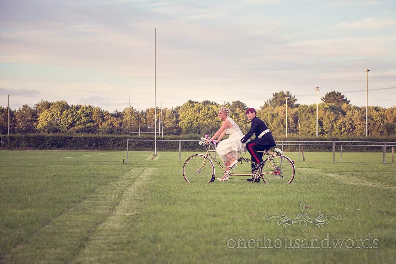 Bride and Groom ride tandem bike at Wareham Rugby Club Wedding