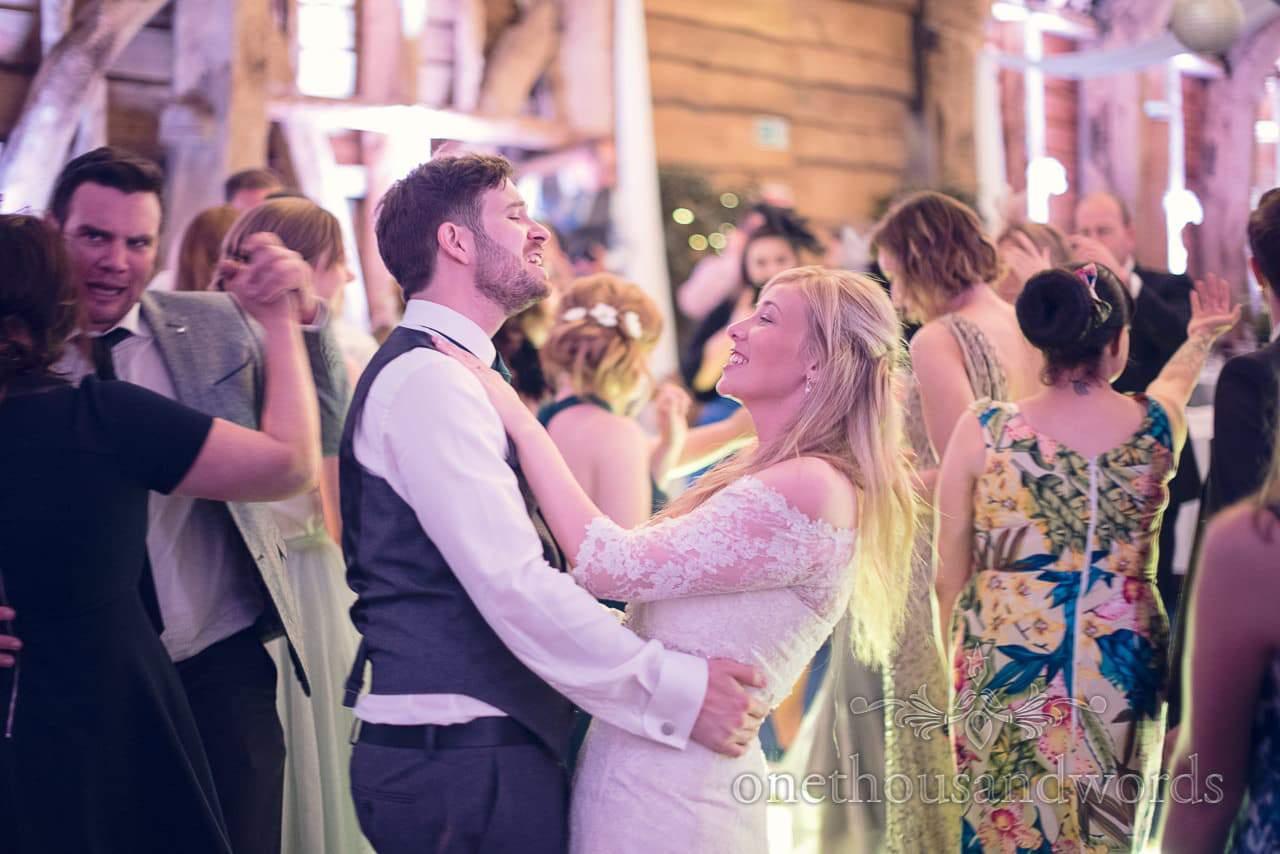 Bride and groom sing to wedding songs amongst dancing guests