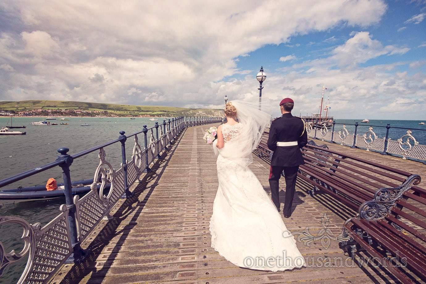Bride and groom walk along Swanage Victorian Pier wedding photograph