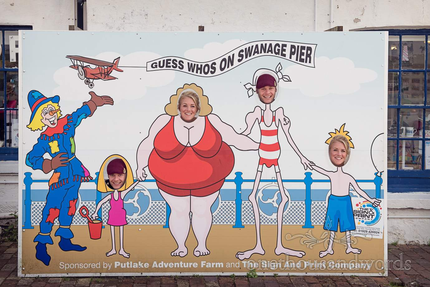 Bride and grooms heads in comedy sign on Swanage Pier, Dorset