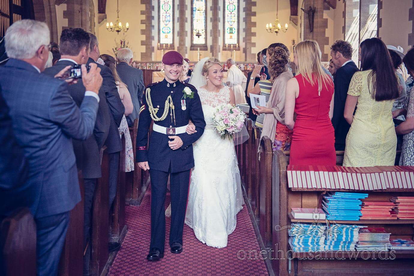 Bride and military groom walk down the aisle at St Marks Church wedding in Swanage