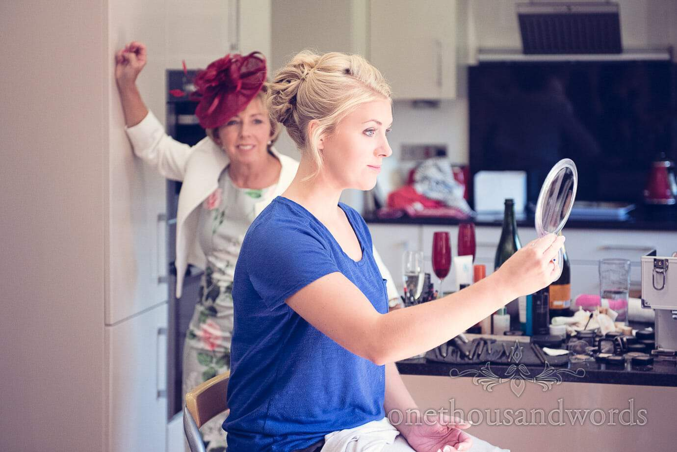 Bride checks her wedding makeup on wedding morning as her mother watches