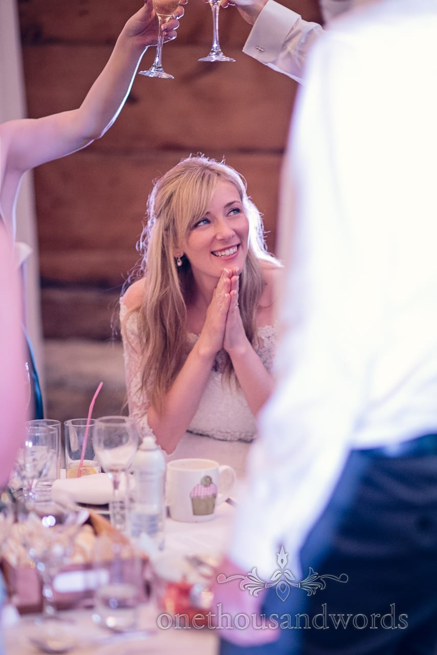 Bride claps at wedding speeches whilst guests raise a toast to her