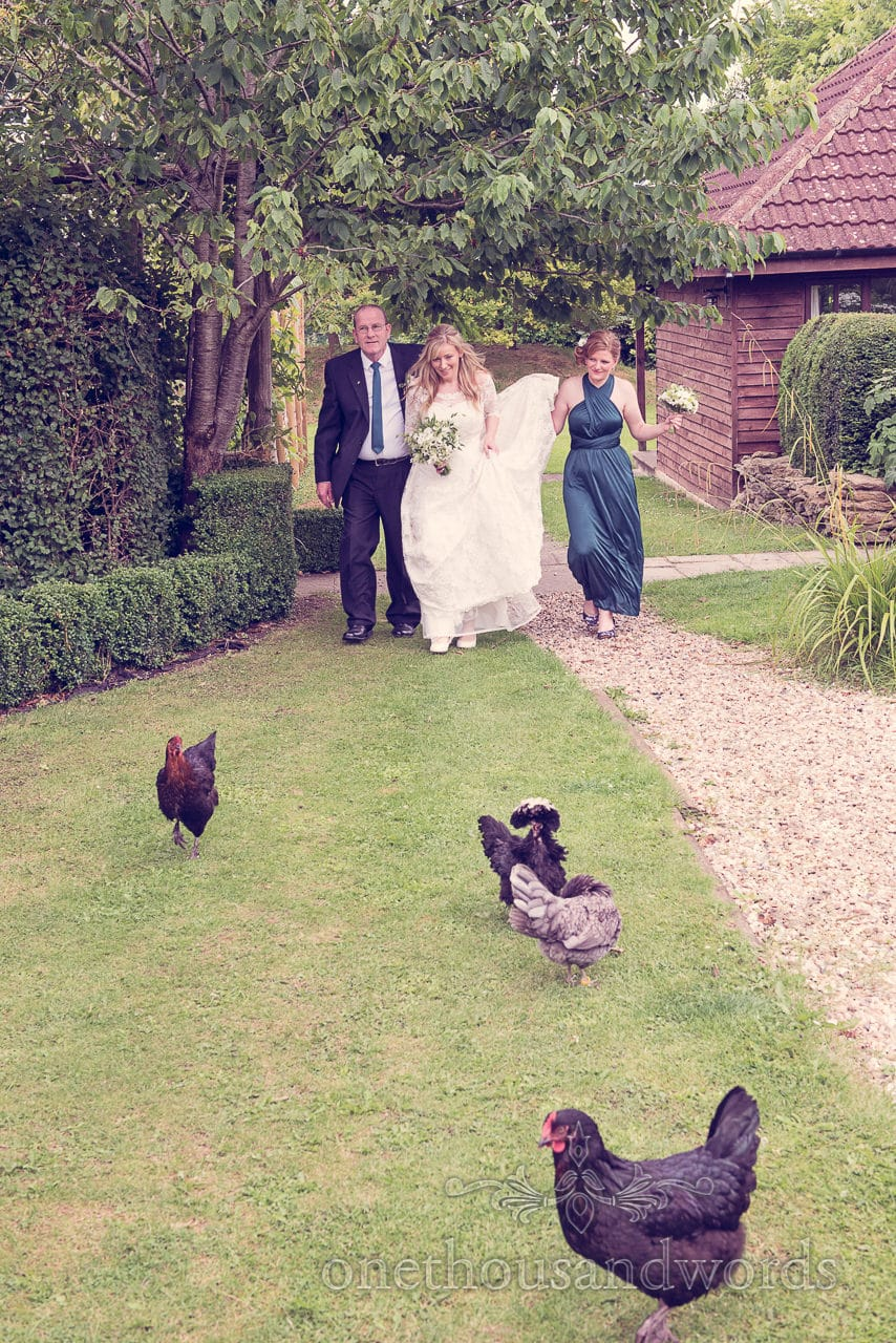Bride, father and bridesmaid walk in wooded garden with chickens