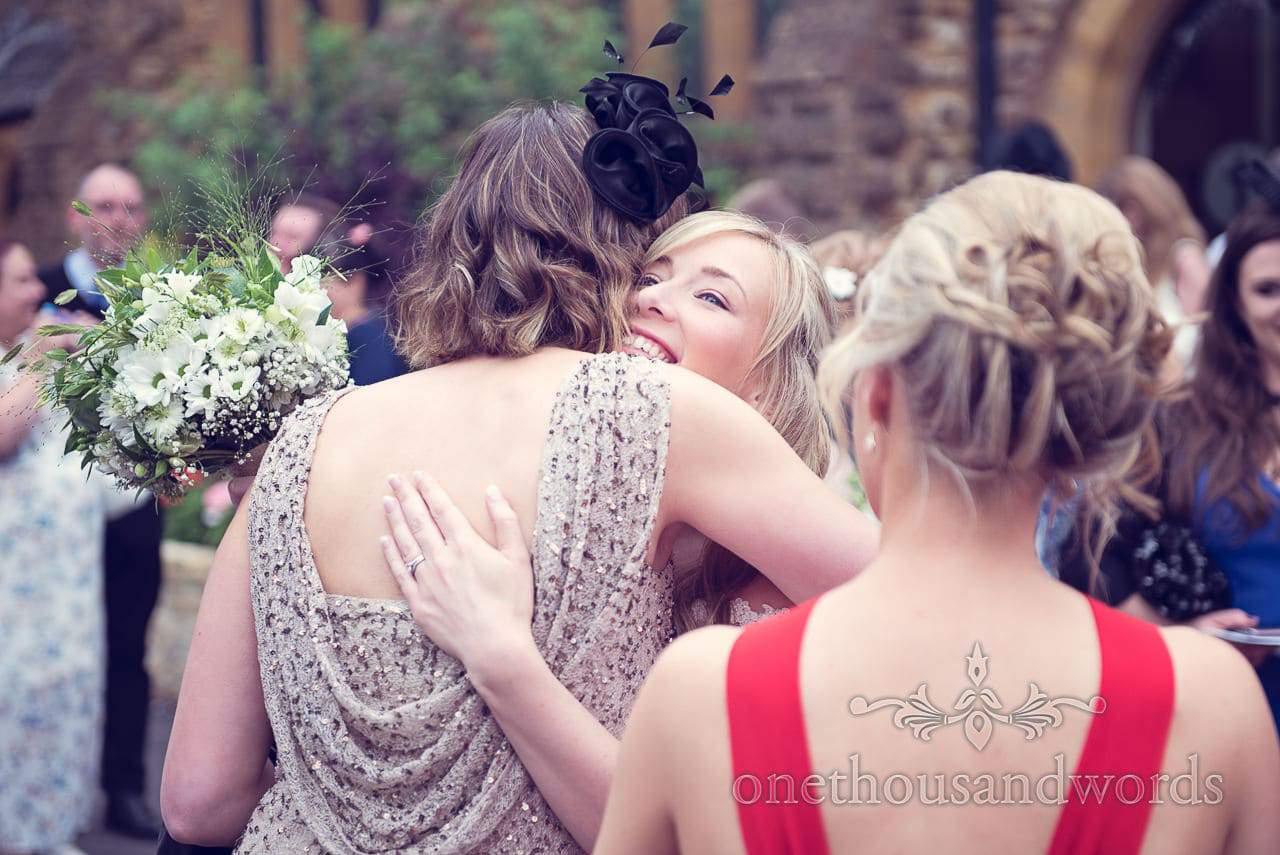 Bride hugs wedding guest outside Catholic church wedding in Sherborne