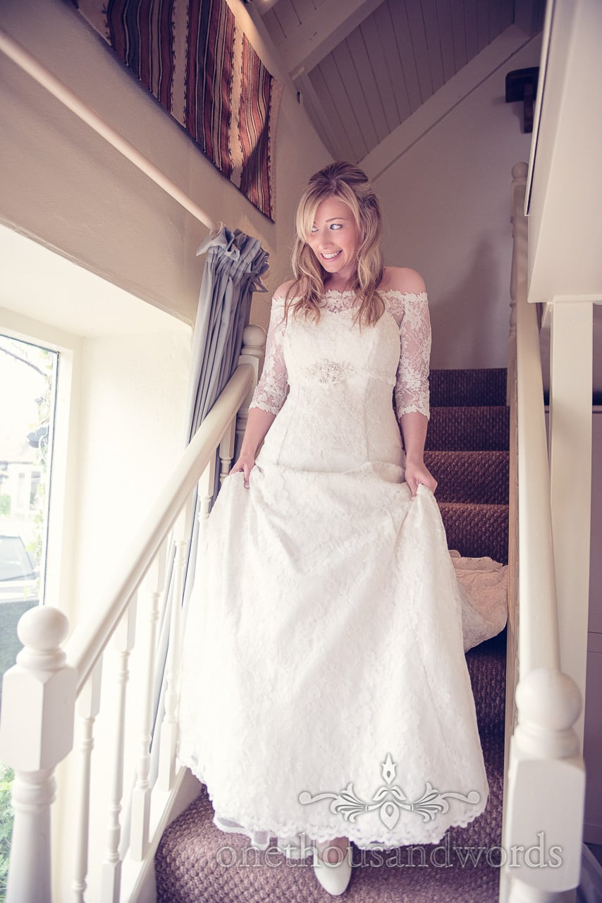 Bride in white detailed wedding dress walks down stairs on wedding morning