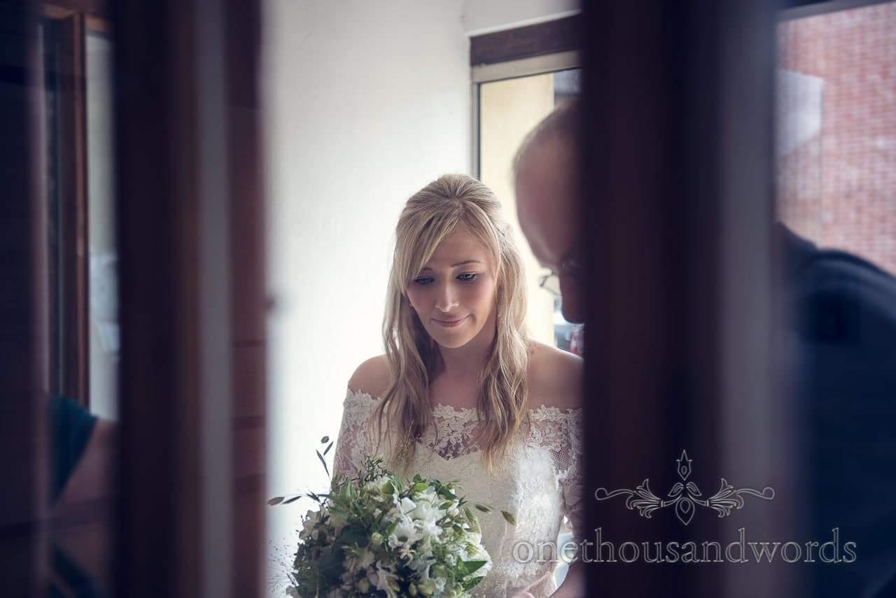 Bride in white wedding dress portrait through door glass outside church
