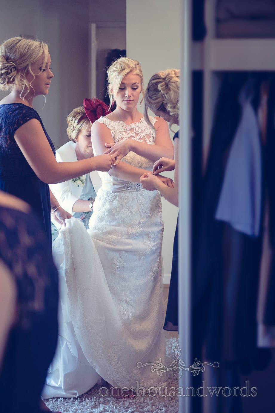 Bride is helped into wedding dress and wedding jewlrey