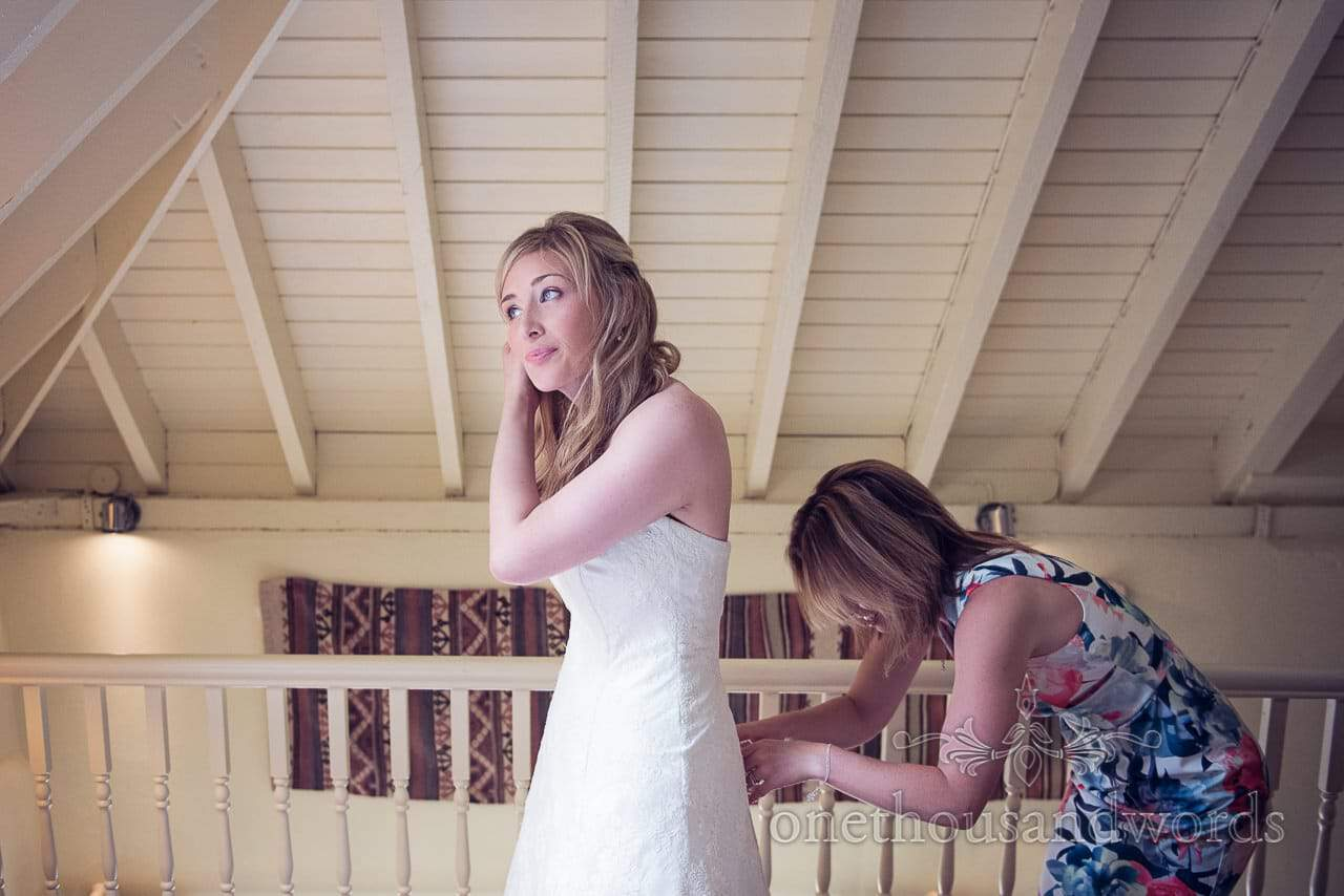 Bride is laced into wedding dress in wooden roof room on wedding morning