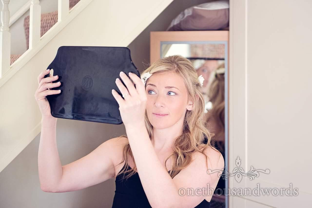 Bride looks at wedding hair in mirror during wedding morning preparations