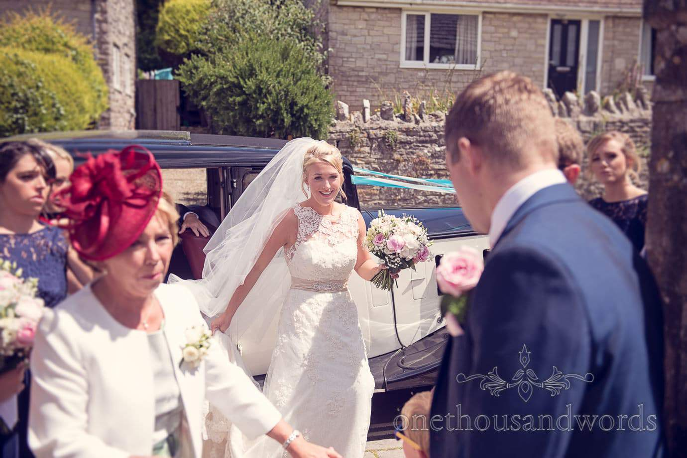 Bride steps out of classic wedding car at Swanage Church wedding