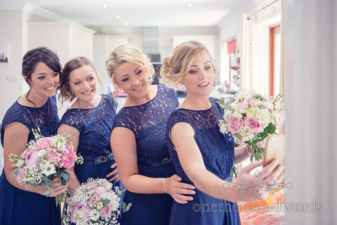 Bridemaids in blue bridesmaids dresses take selfie on wedding morning