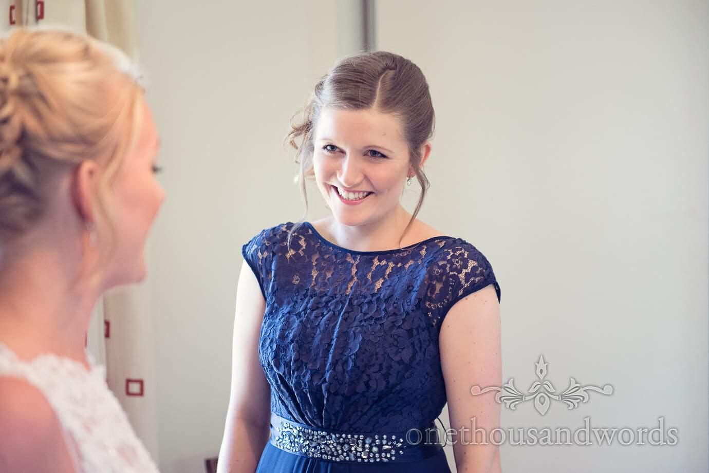 Bridesmaid in blue detailed bridesmaid dress smiles at bride
