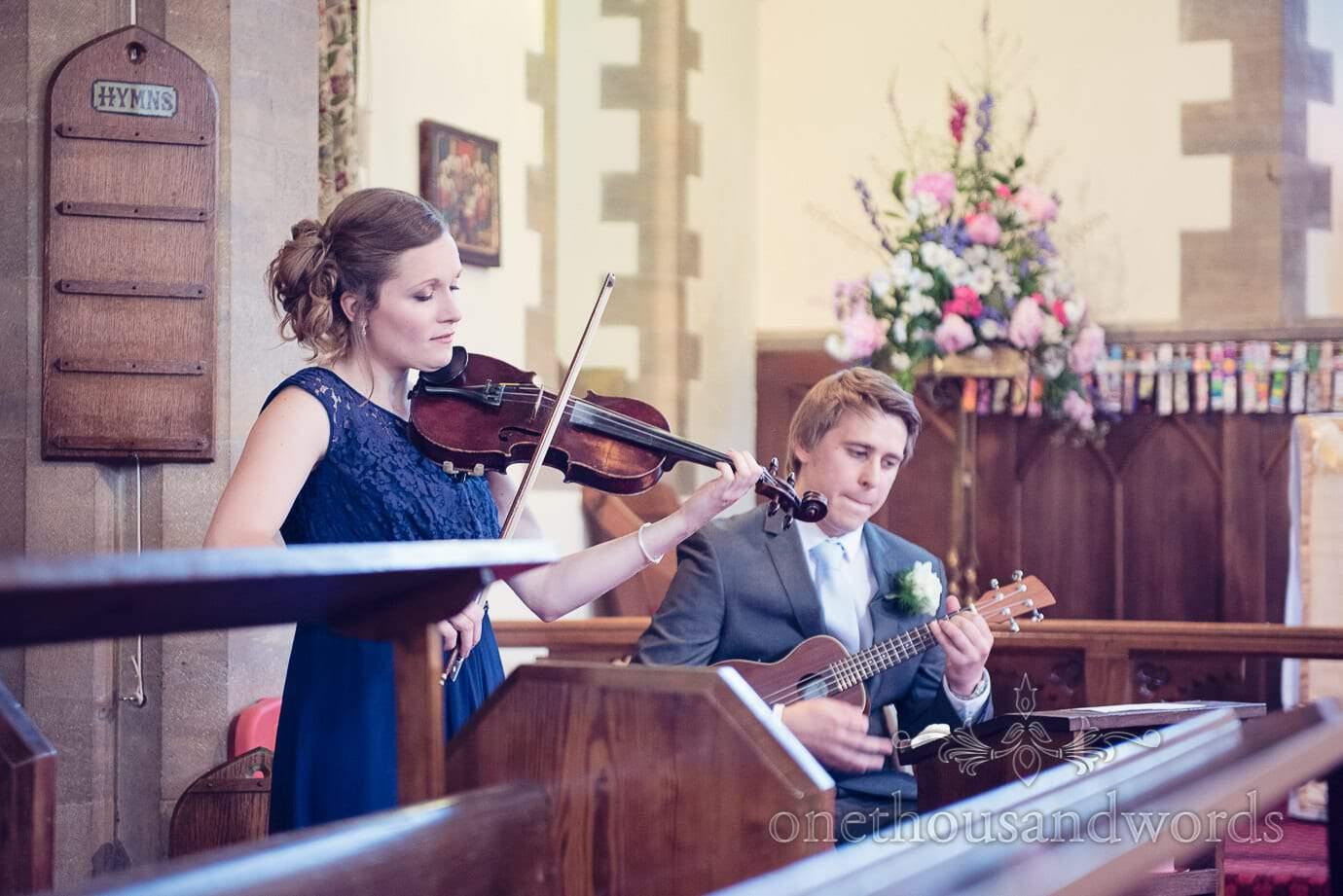 Bridesmaid in blue dress plays violin at Swanage church wedding