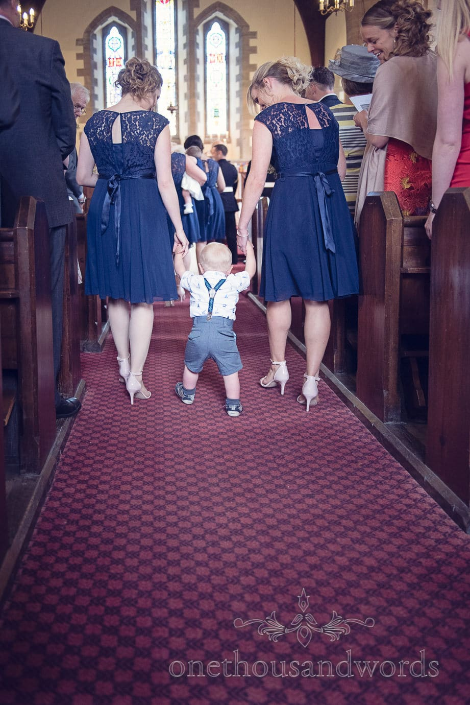 Bridesmaids in blue walk pageboy in braces up the aisle at Swanage Church wedding