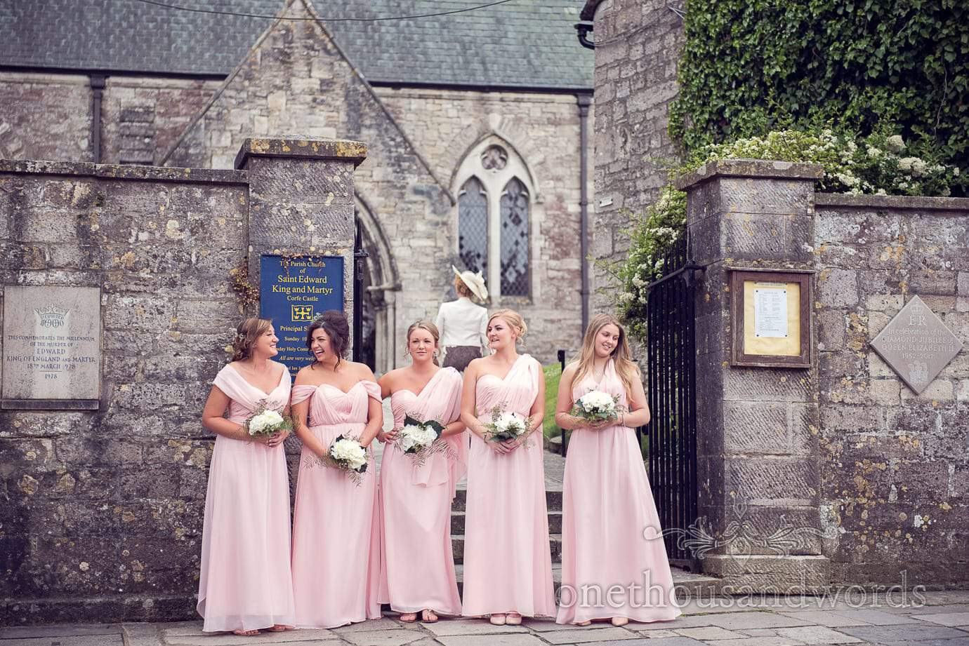 Bridesmaids in pink greco roman bridesmaids dresses outside Corfe Castle church