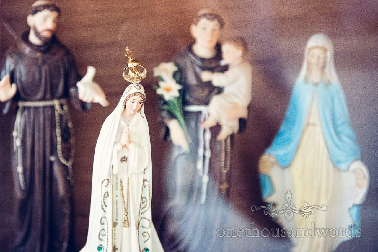 Catholic religious figurines of noah and the virgin mary at wedding venue