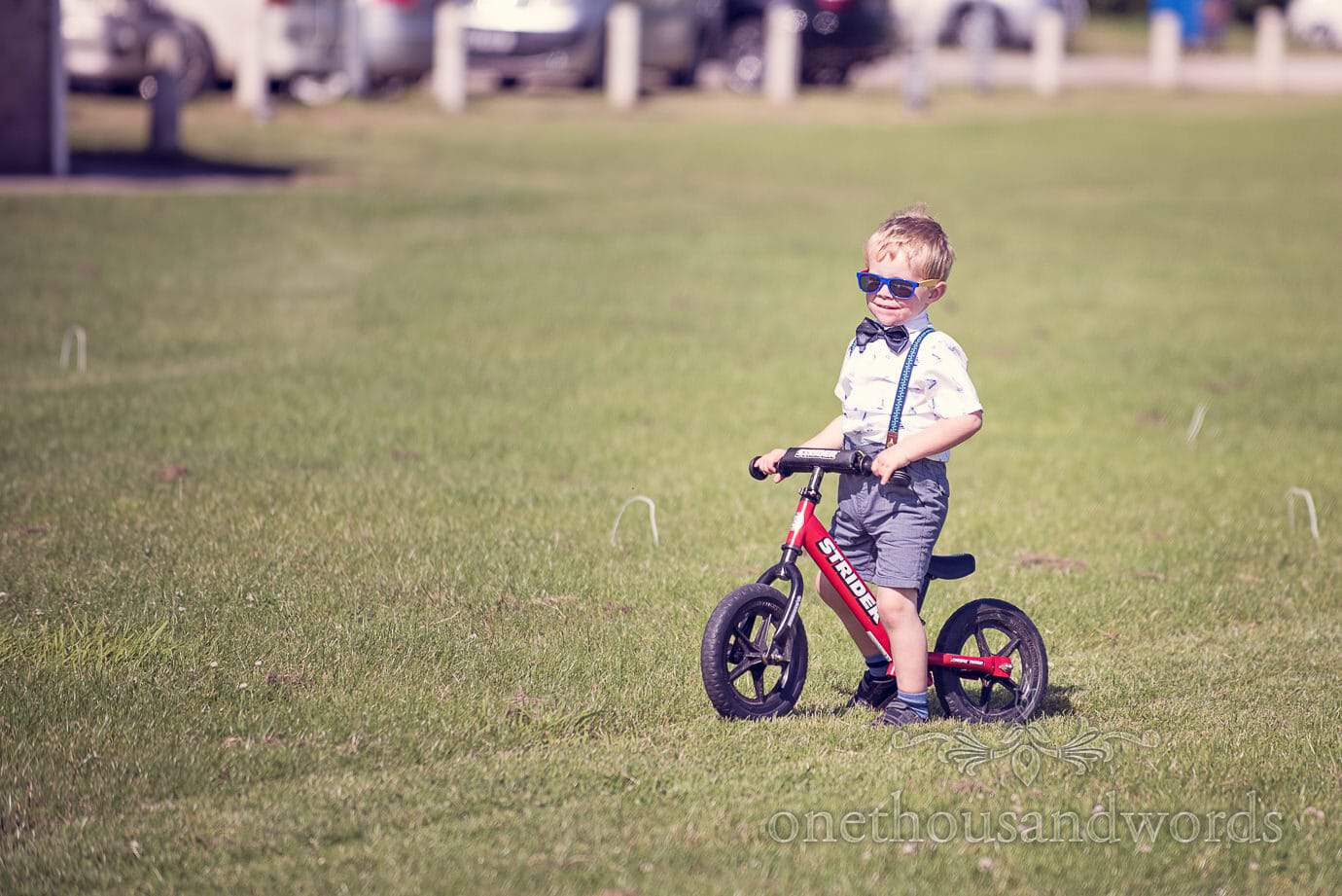Child wedding guest in bow tie and braces rides bike at drinks reception
