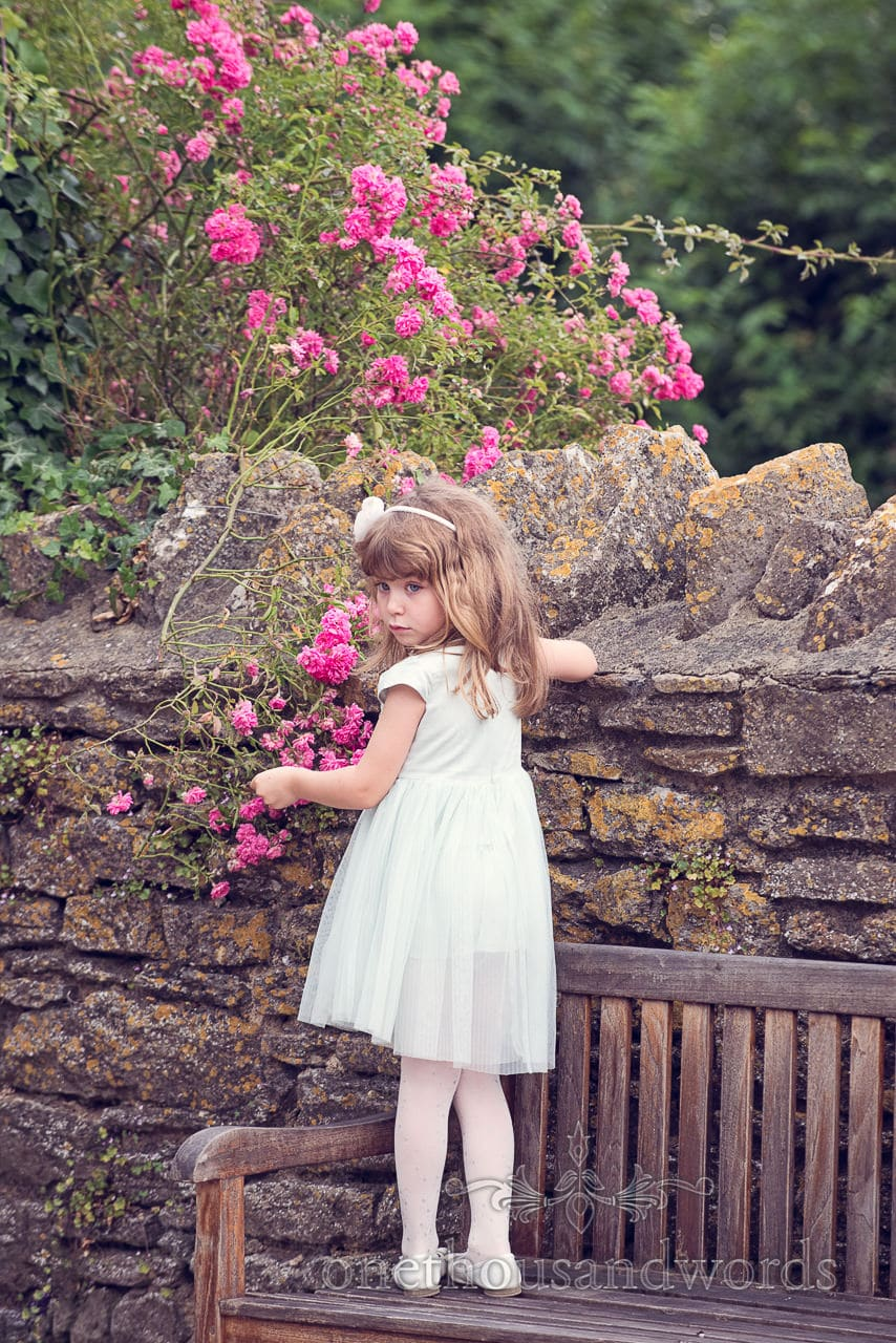 Child wedding guest plays with flowers at barn wedding venue