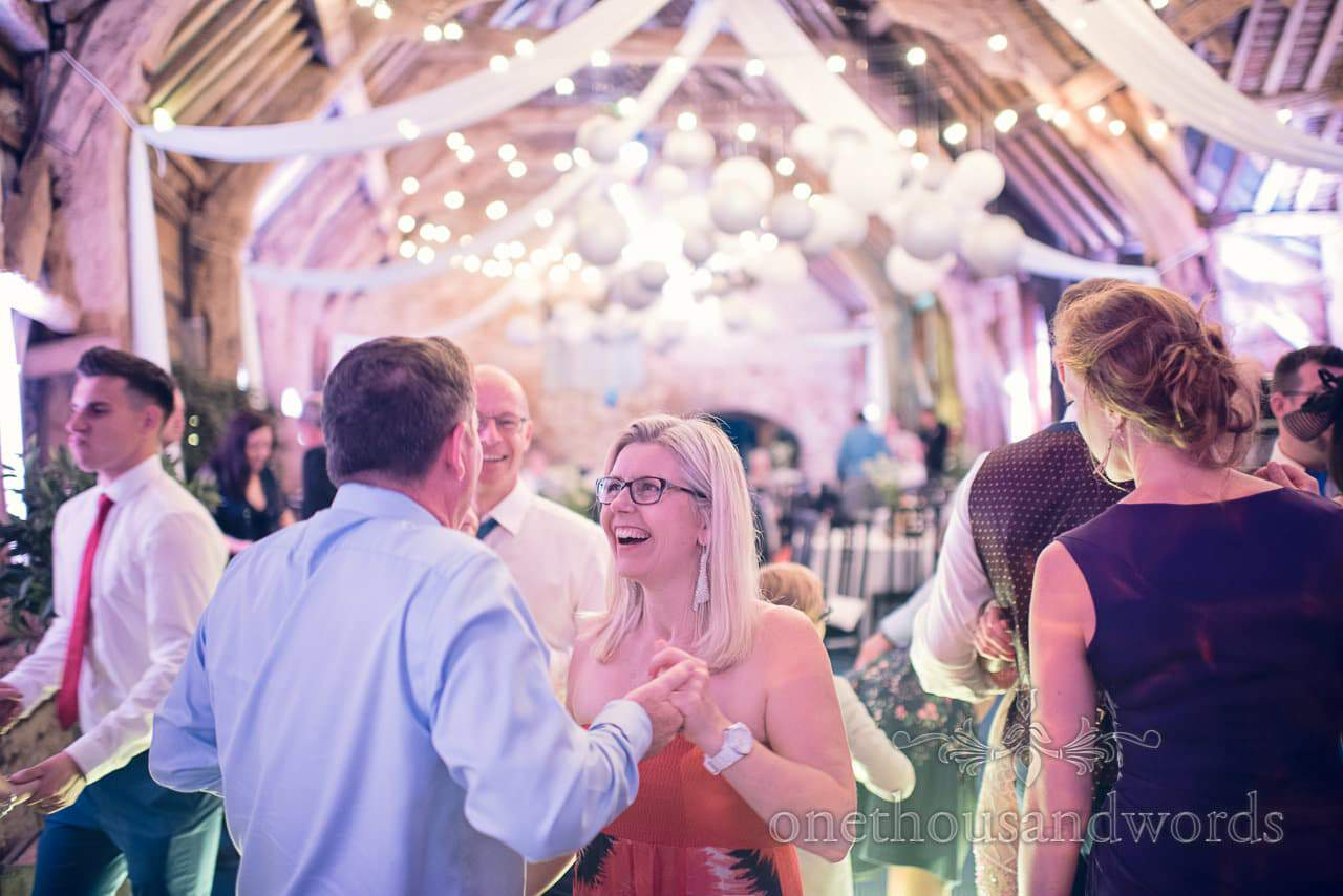 Dancing at barn wedding venue with bright fairy lights and chinese lanterns