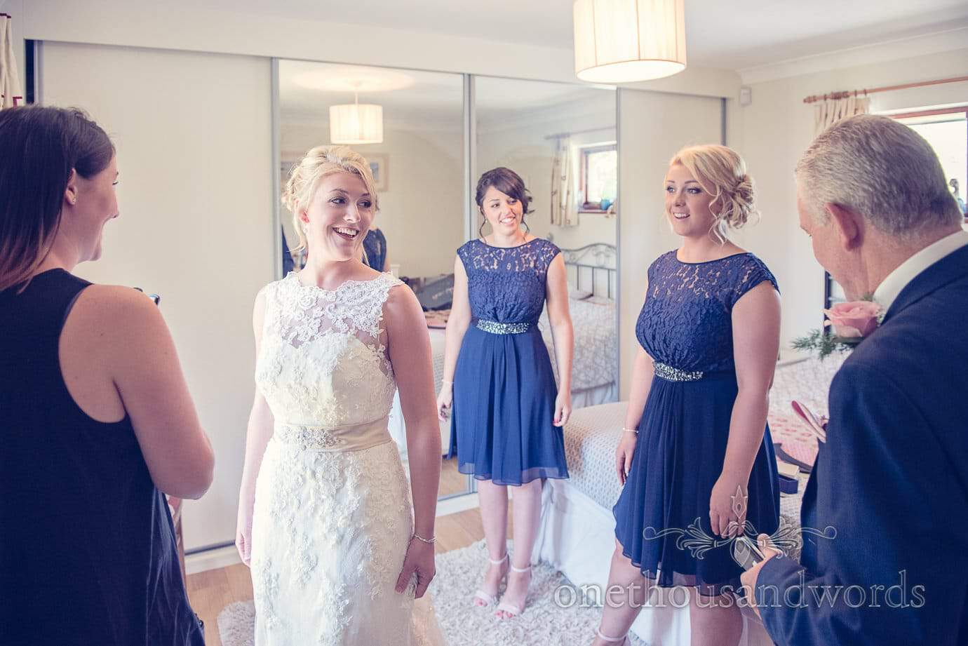 Documentary photograph of Bridesmaids looking at bride in white wedding dress