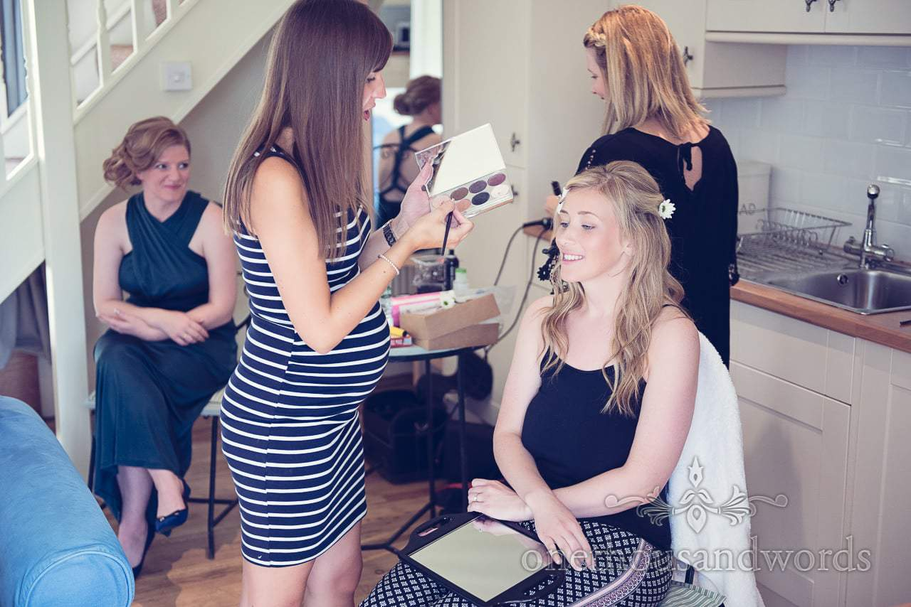 Bride having wedding hair and makeup styled while bridesmaid watches