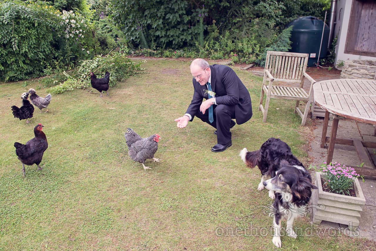 Father of bride with chickens and dog on wedding morning in Dorset