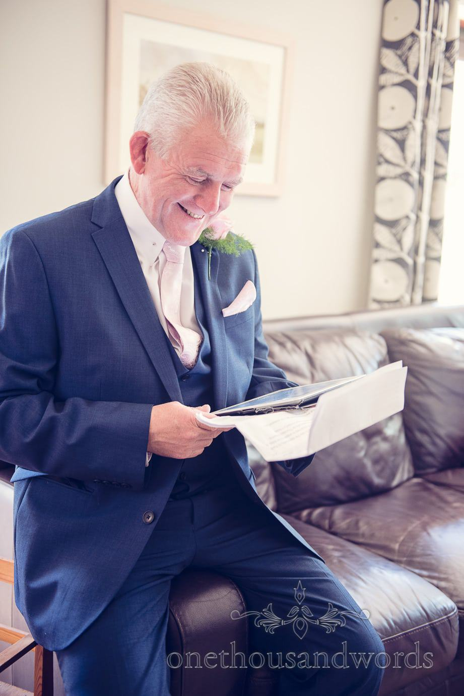 Father of the bride in blue wedding suit practices his wedding speech