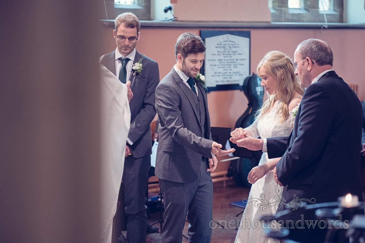 Father of the bride passes her hand to groom during Catholic wedding ceremony