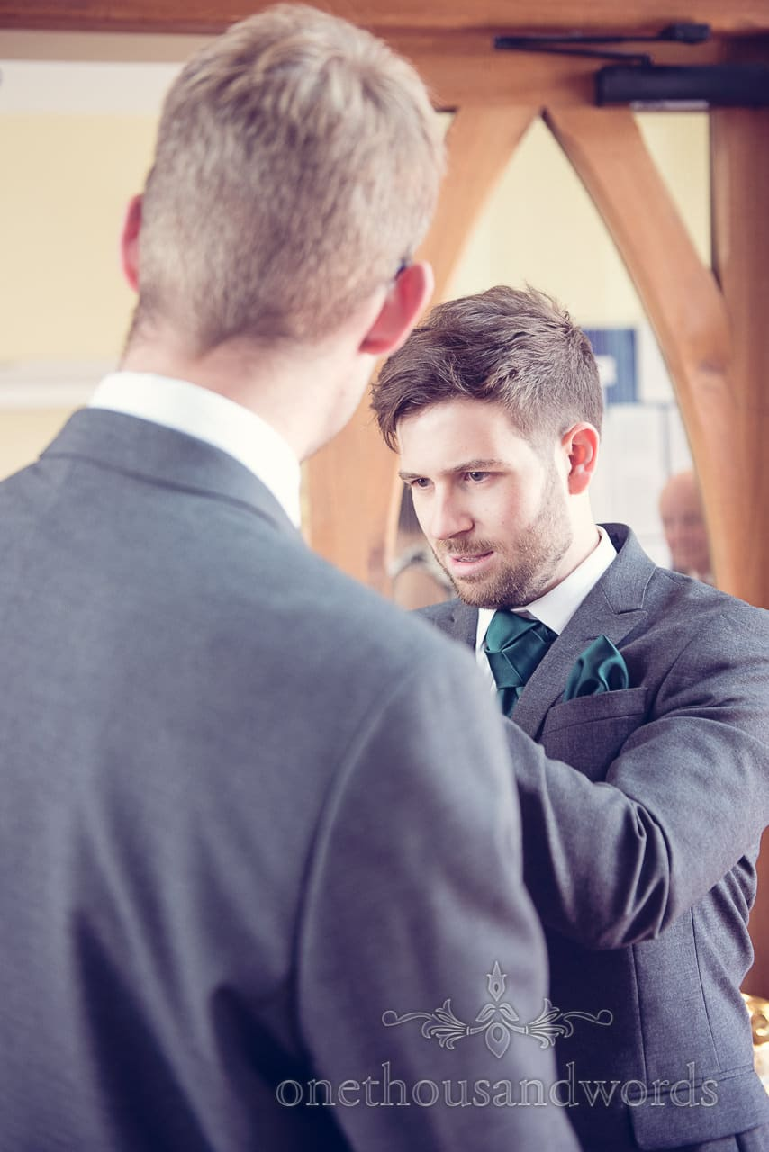 Groom adjust best mans wedding button hole with face of concentration