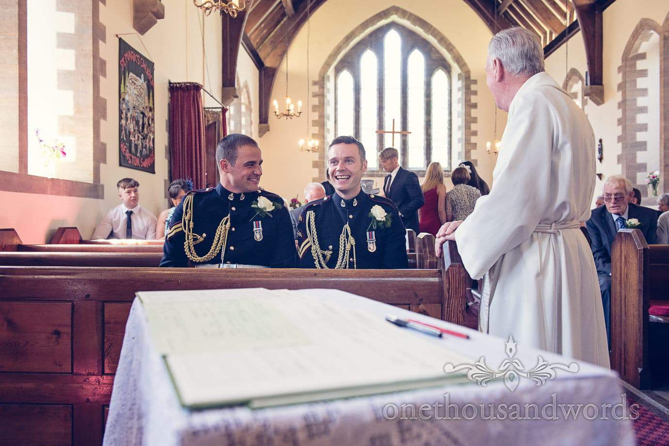 Groom and best man in military uniform laugh in church