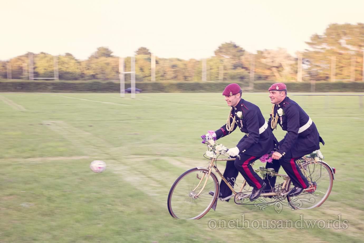 Groom and best man in military unifor ride tandem wedding bike