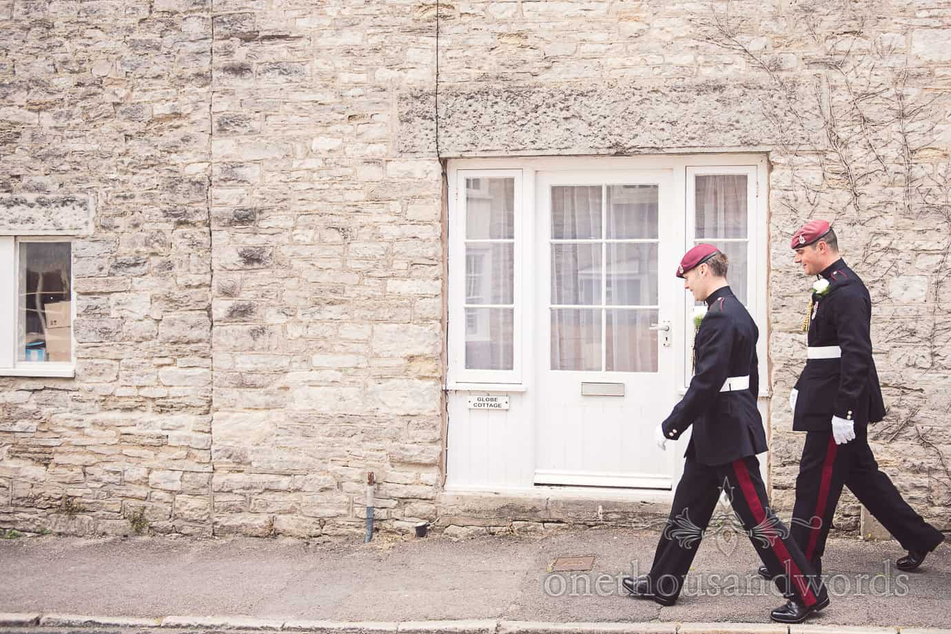 Groom and best man in military uniform walk to pub on wedding morning