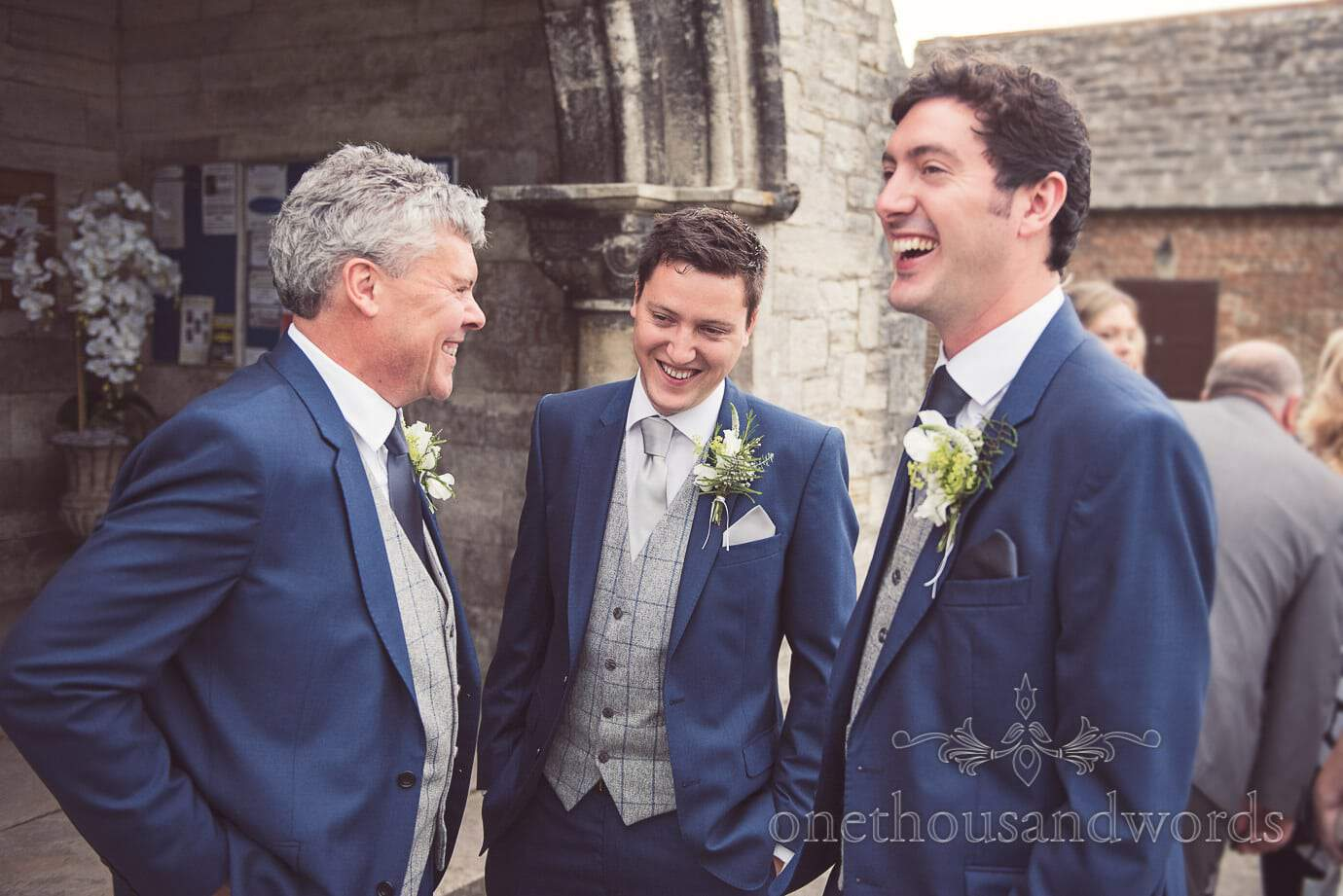 Groom and groomsmen in blue wedding suits outside Corfe Castle Church