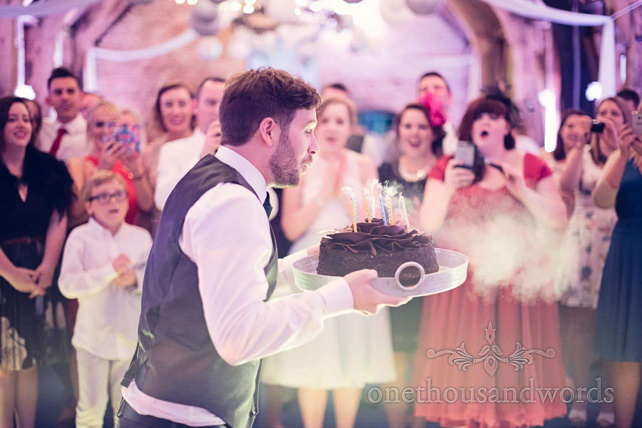 Groom blows out candles on birthday cake while guests watch at wedding