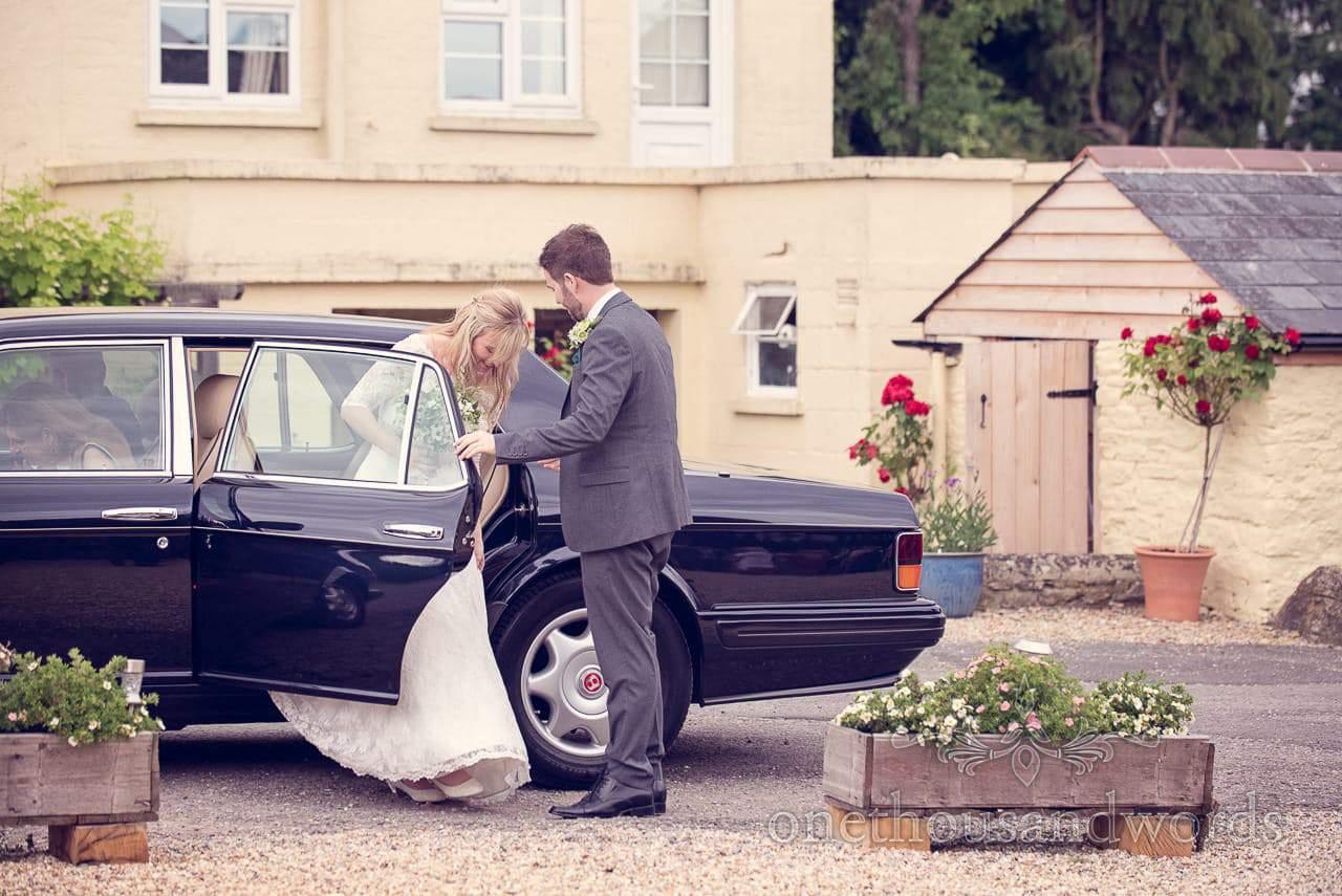 Groom helps bride out of Bentley wedding car