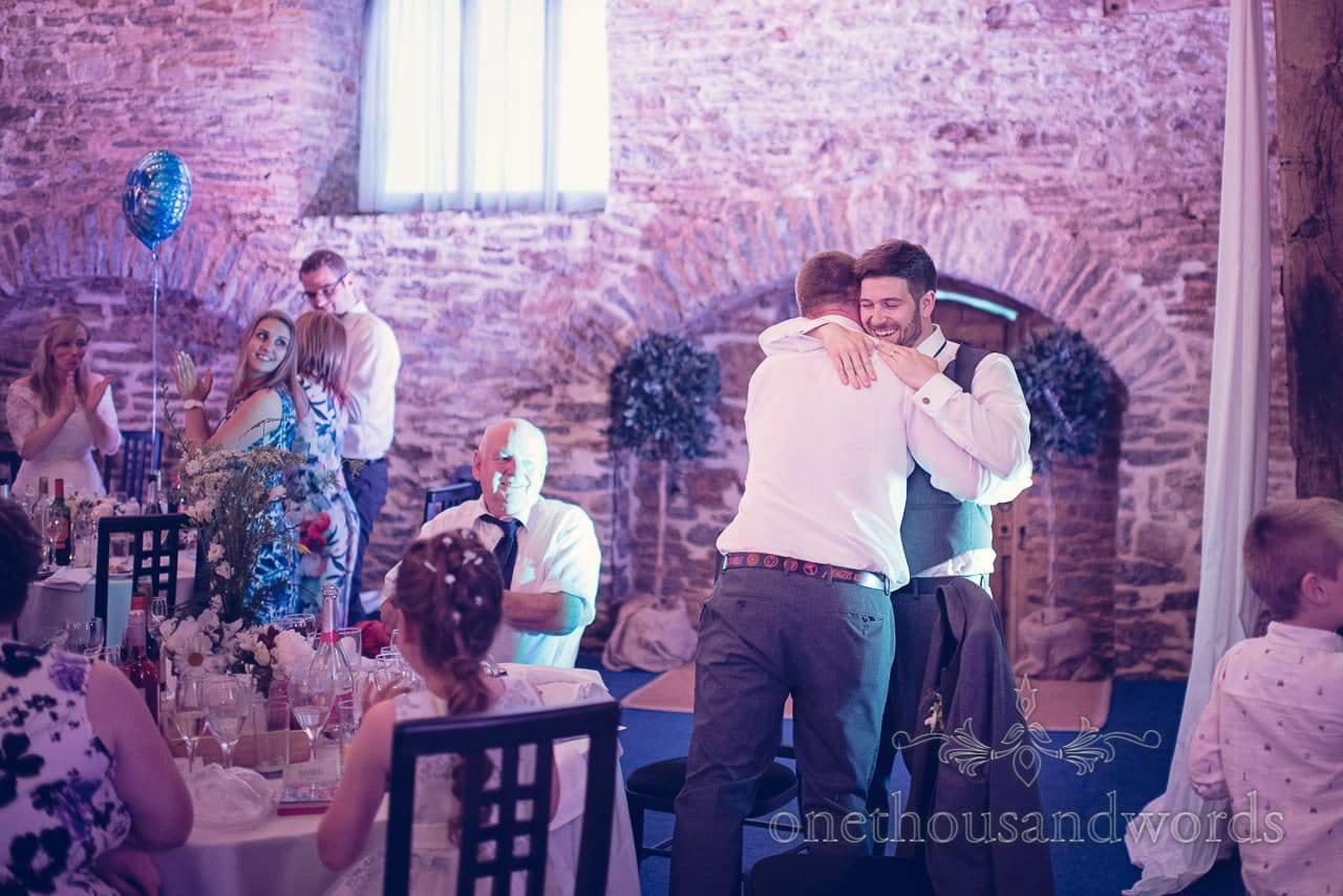 Groom hugs his best man/ brother after wedding speech in wedding Barn