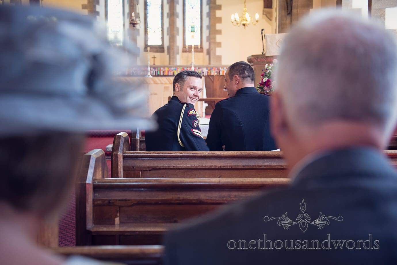 Groom in church looks over shoulder to check on wedding guests